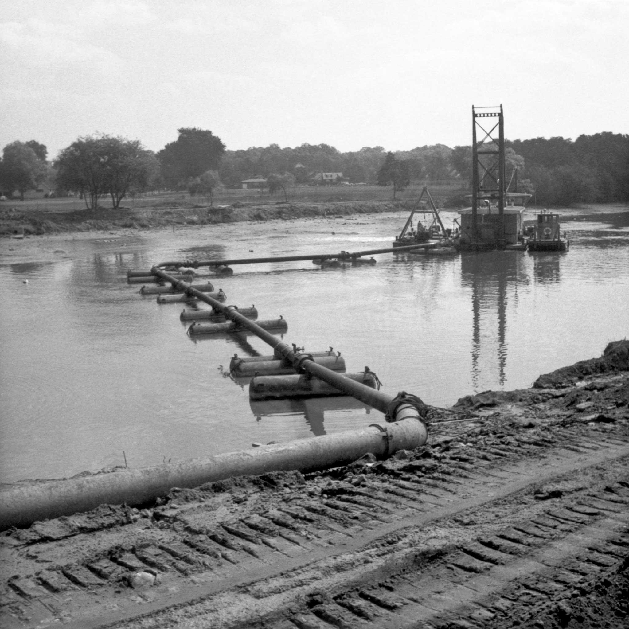 black and white image of pontoons and a pumping derrick in a body of water with trees in the background and railroad in the foreground