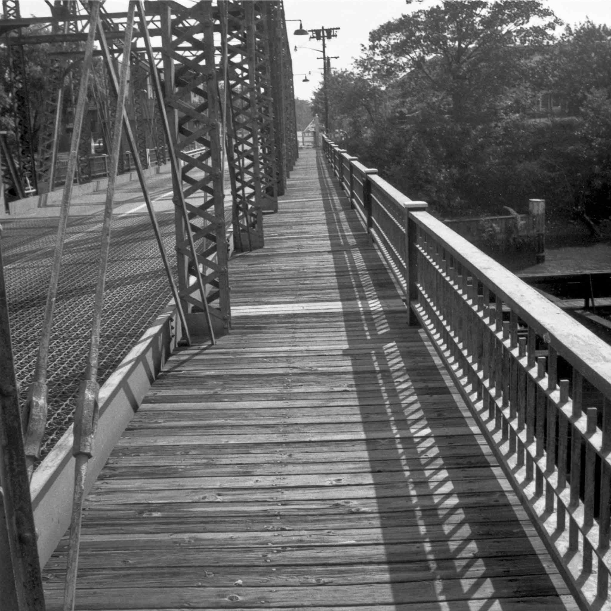 black and white image of a wooden walkway on a metal truss bridge with trees in the background
