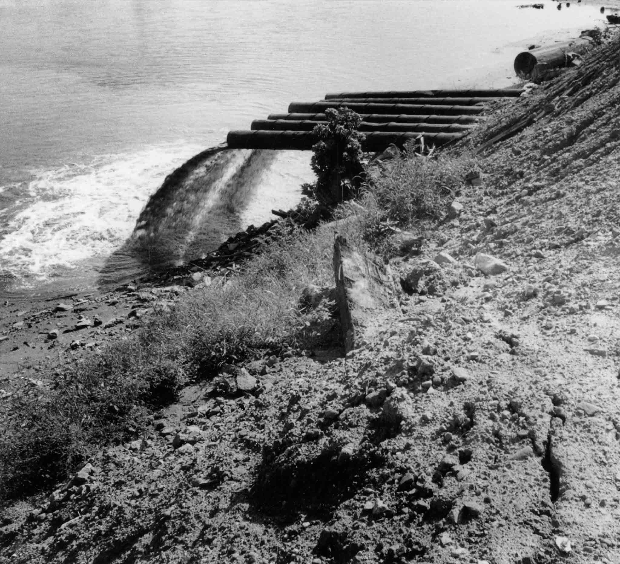 black and white image of several pipe jutting out of an earthen bank and dumping water into a body of water