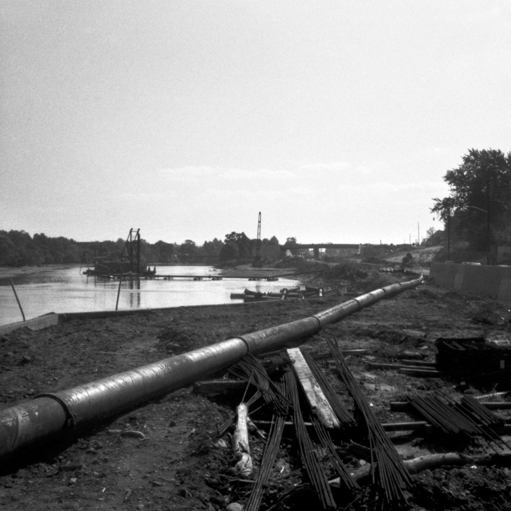 black and white image of a large metal pipe next to a body of water and landscape in the background