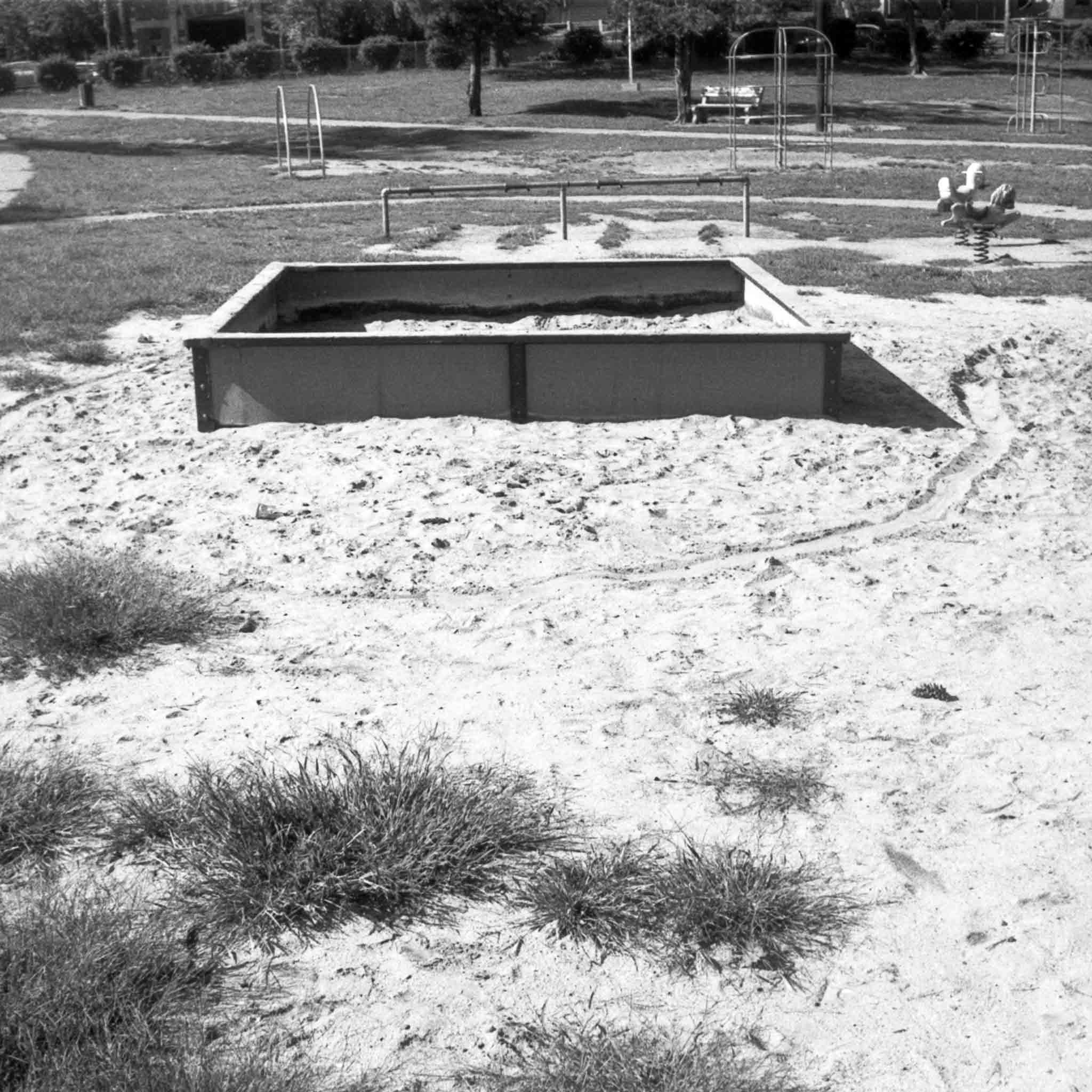 black and white image of a sandbox with a playground in the backgroud