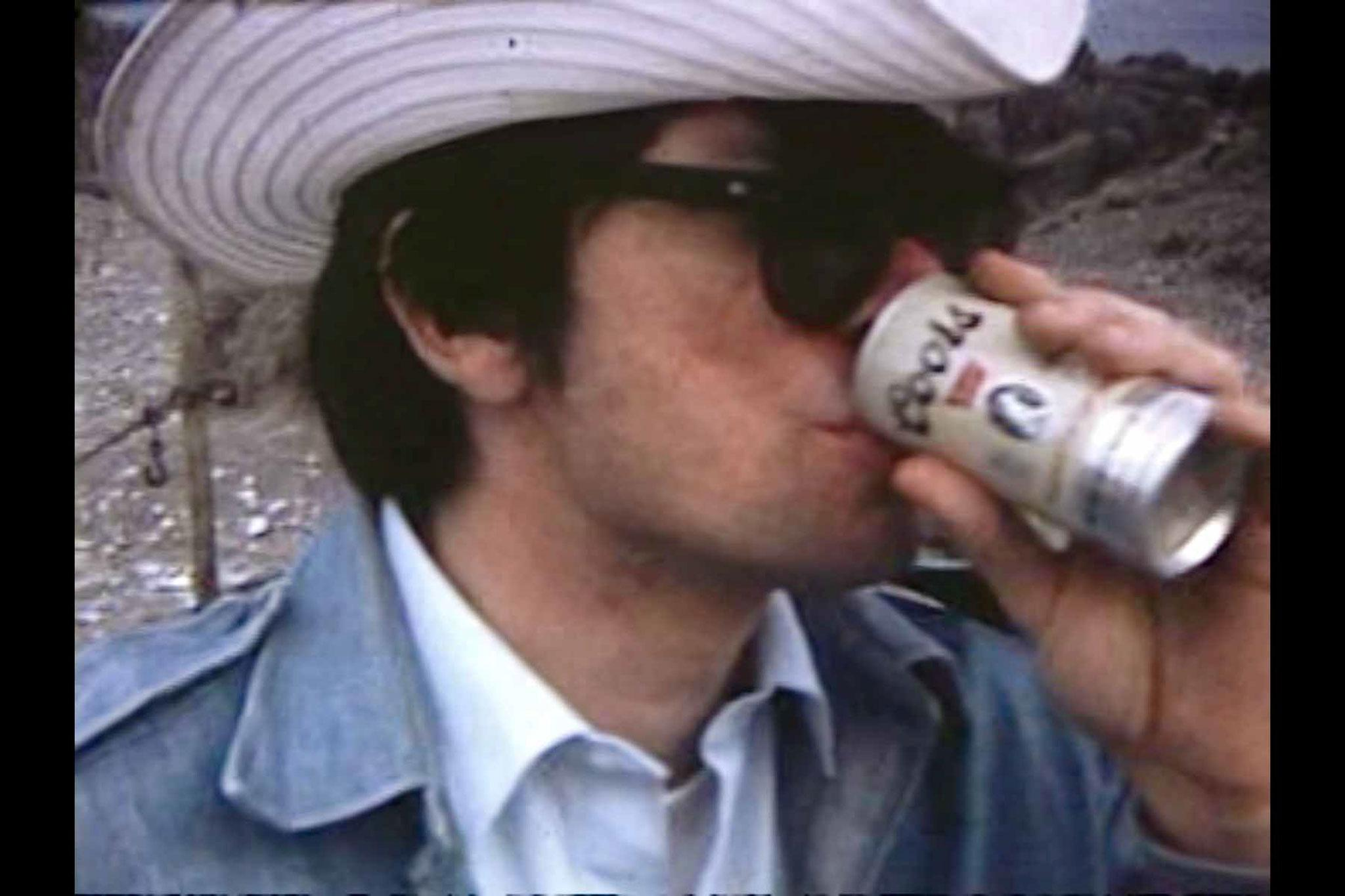 A man wearing a cowboy hat drinking a Coors beer
