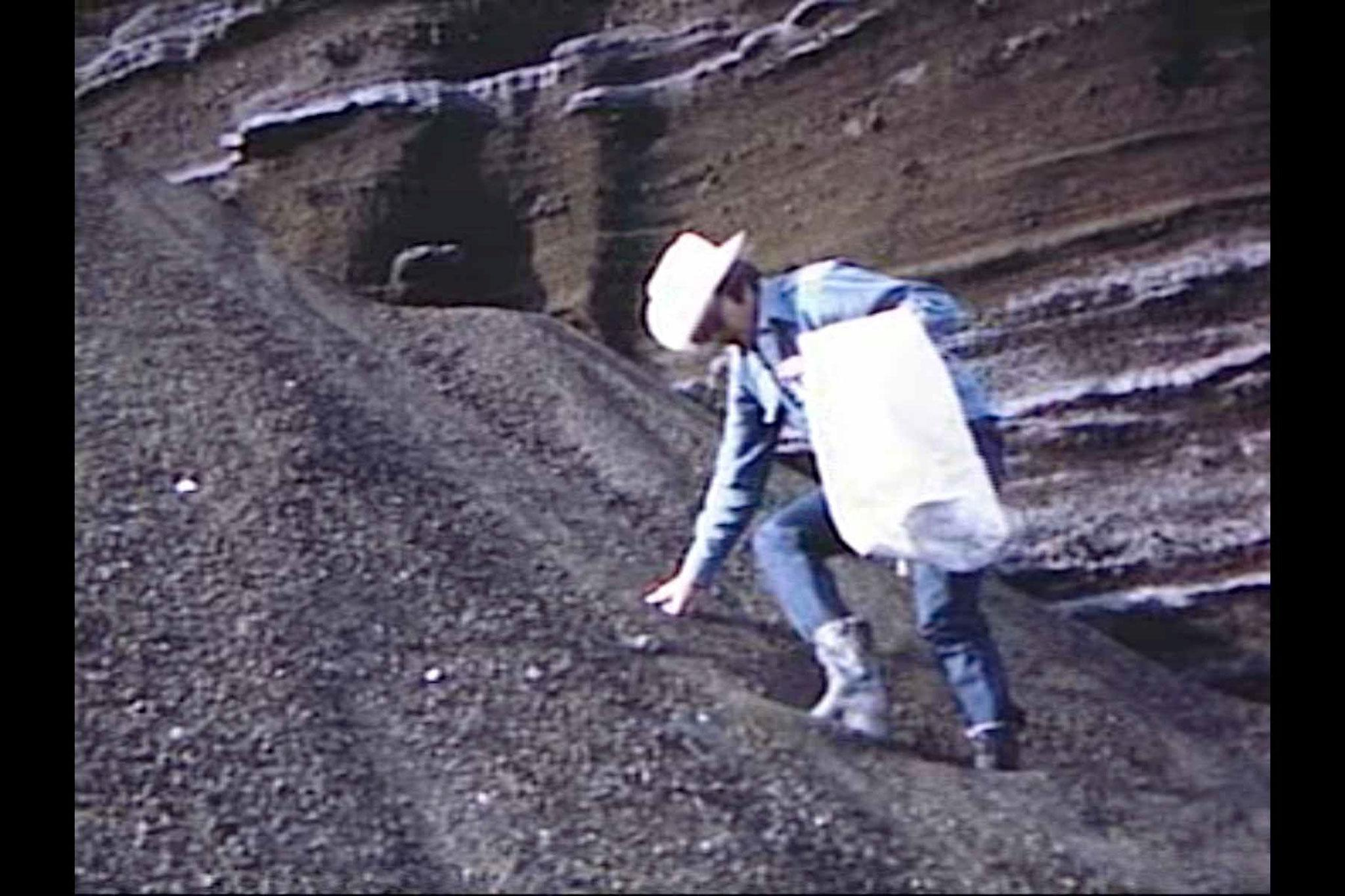A man wearing a cowboy hat descending a steep slope of gravel