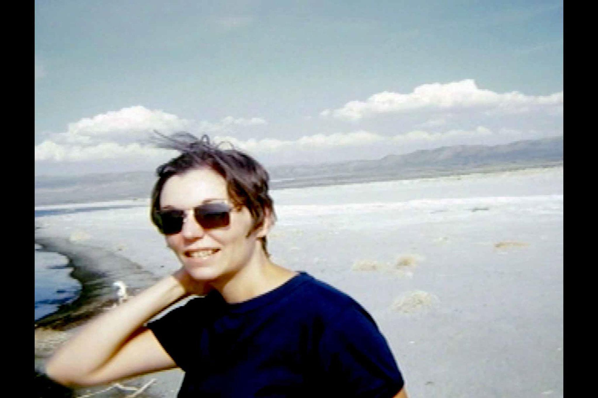 A young woman wearing sunglasses looking at the camera, with blue sky and desert behind her.