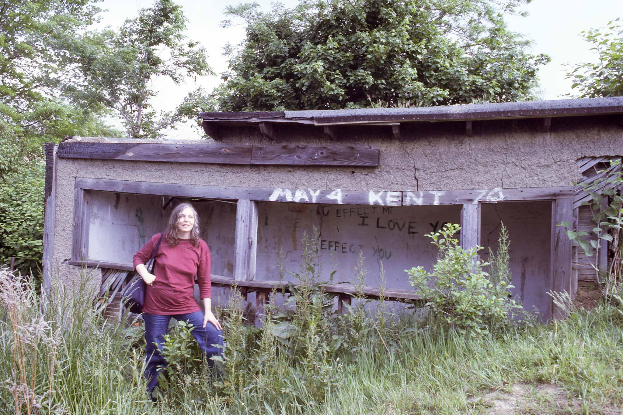 A woman stands next to a dilapidated woodshed with earth piled on the right wall and roof has been taken over by the surrounding plants