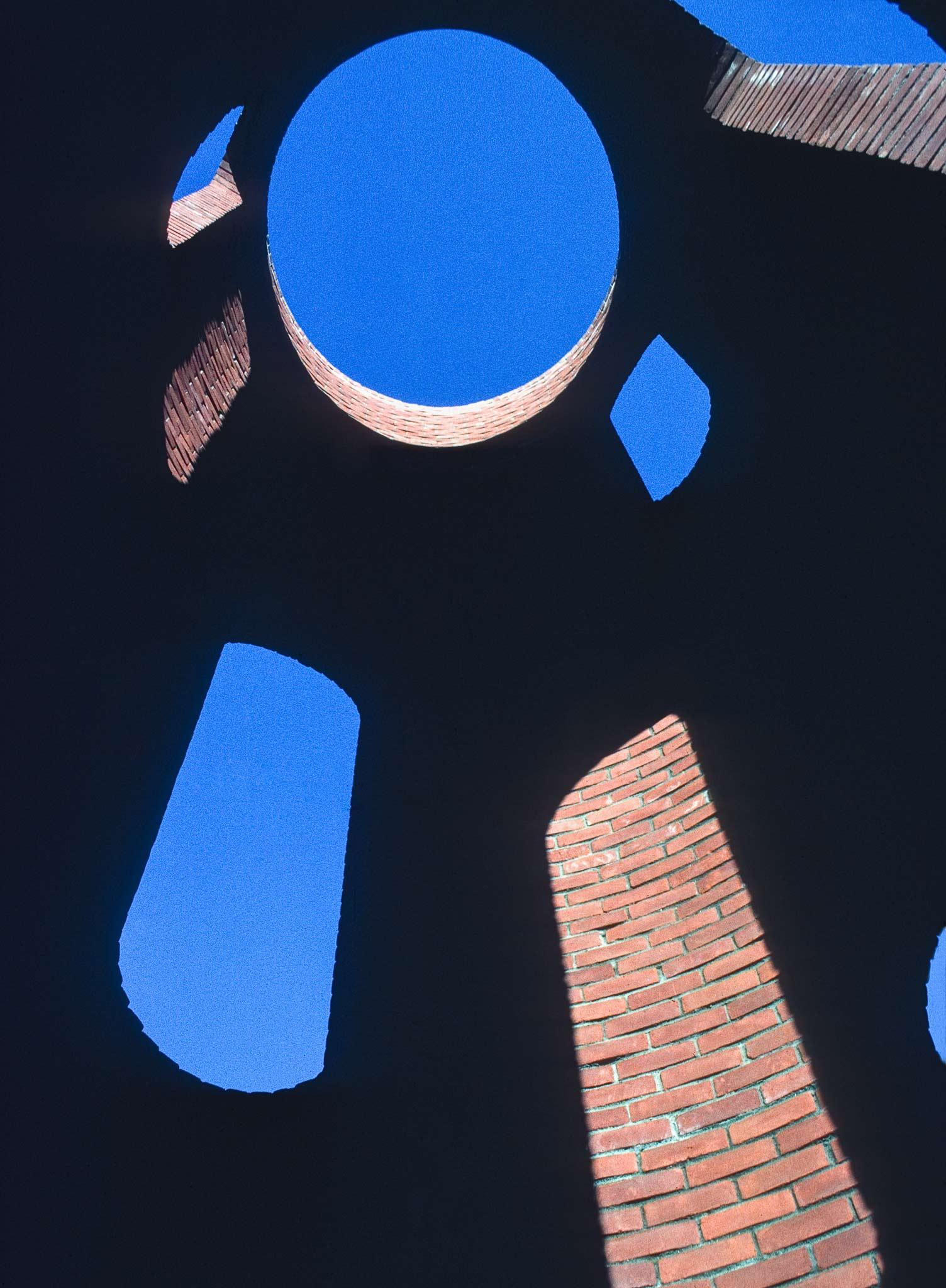 Interior view of a tall circular brick structure with a circular oculus at the top
