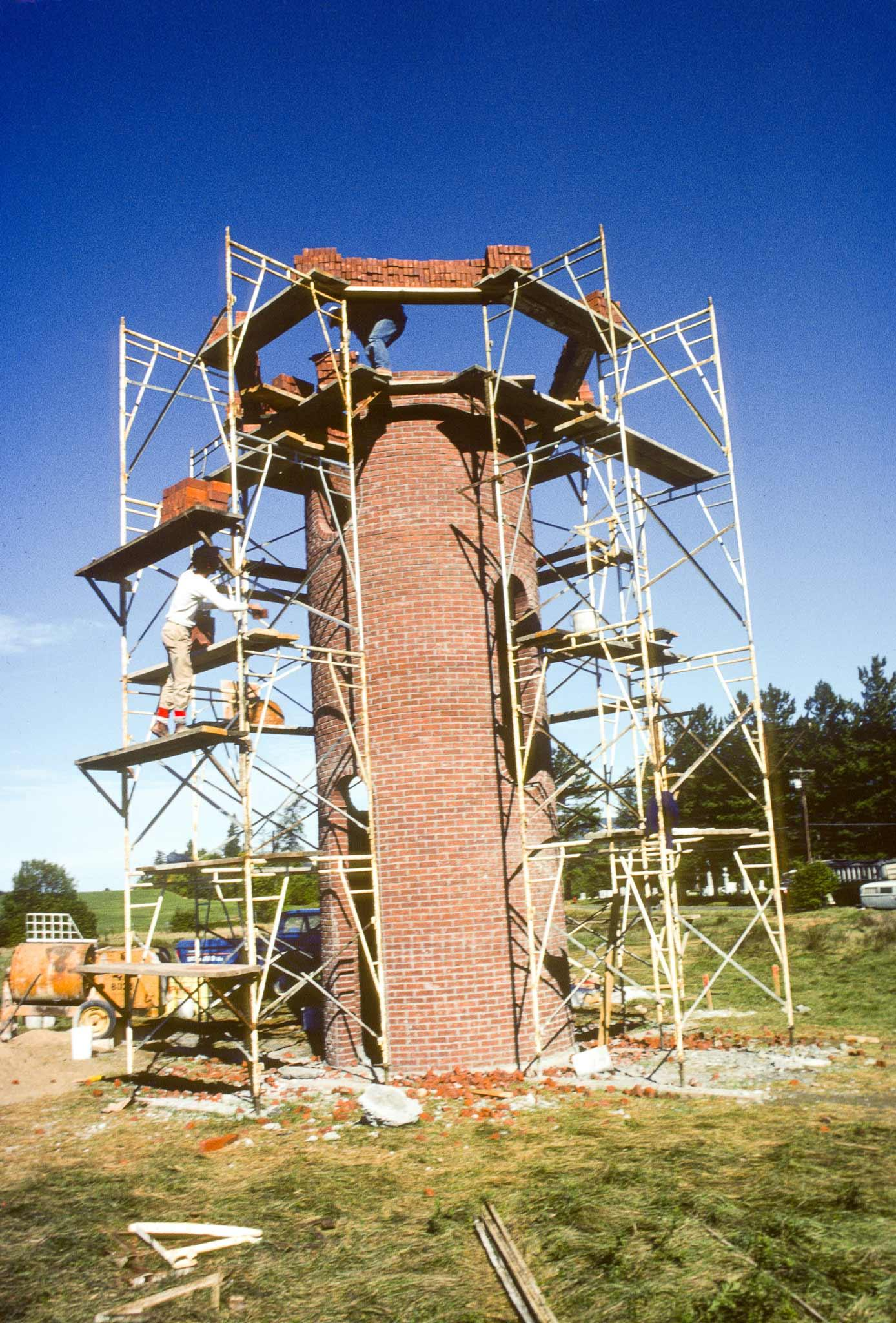 construction image of scaffolding surrounding a tall circular brick structure