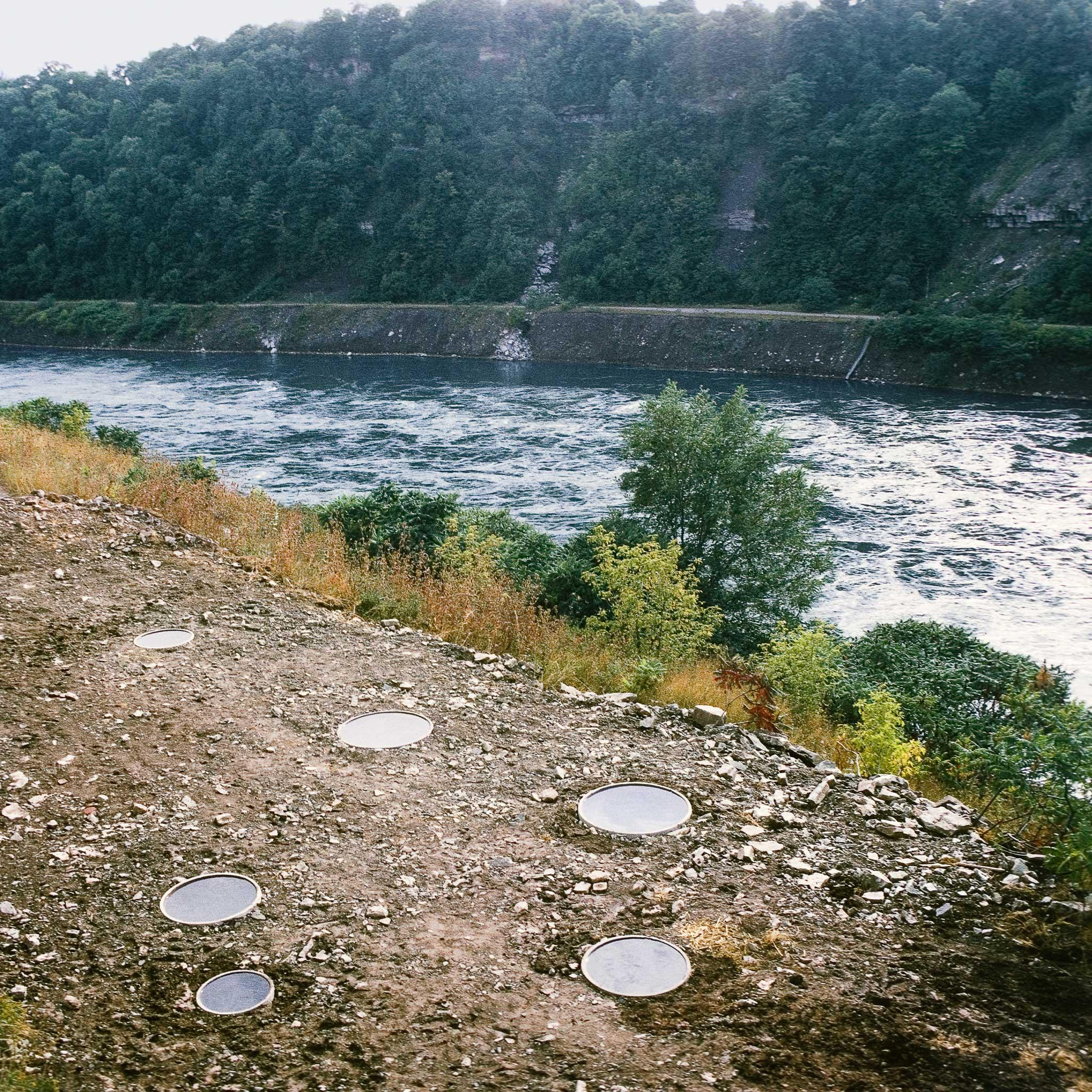 A series of small circular pools in the position of the constellation Hydra along a river bank. River and woods beyond in the background.