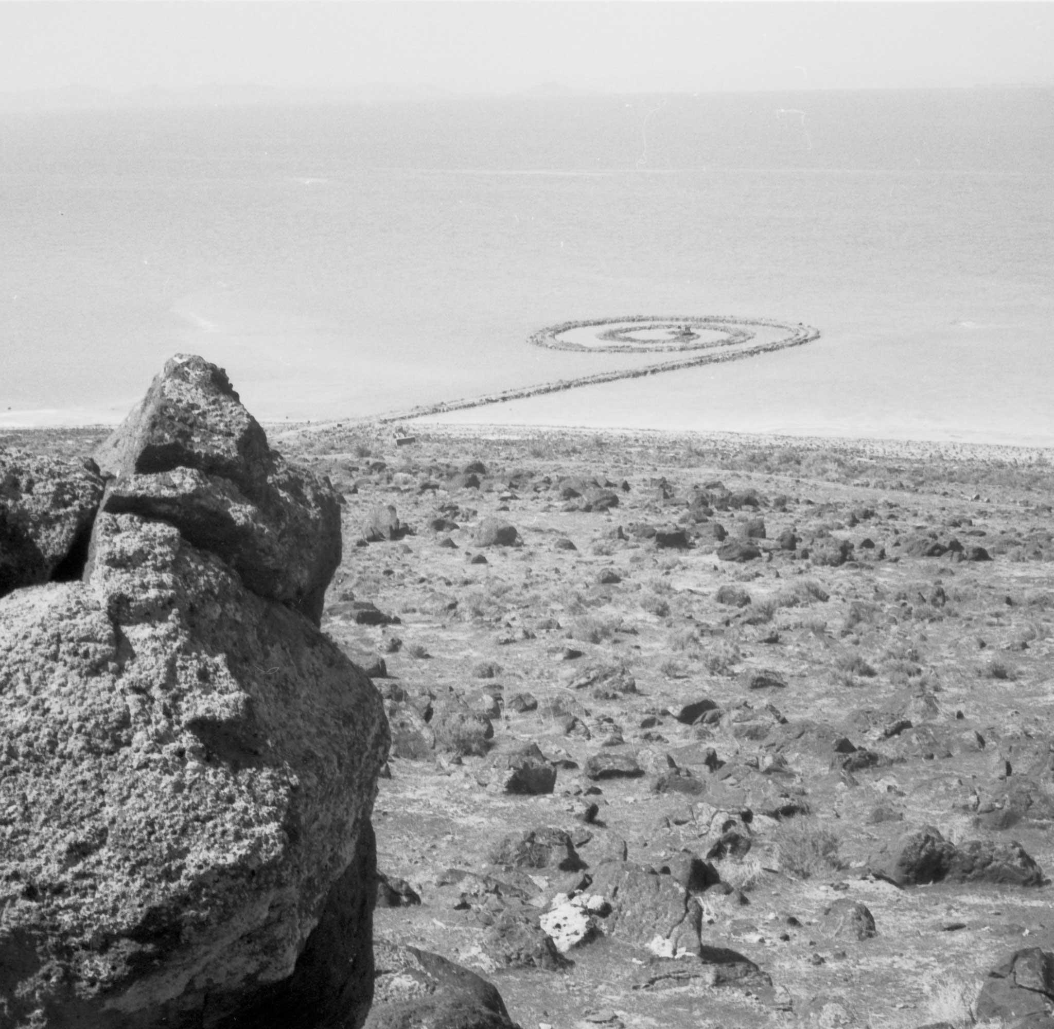 black and white image showing a spiraling jetty of rock extending out into a lake, with the shoreline and rocks in the foreground