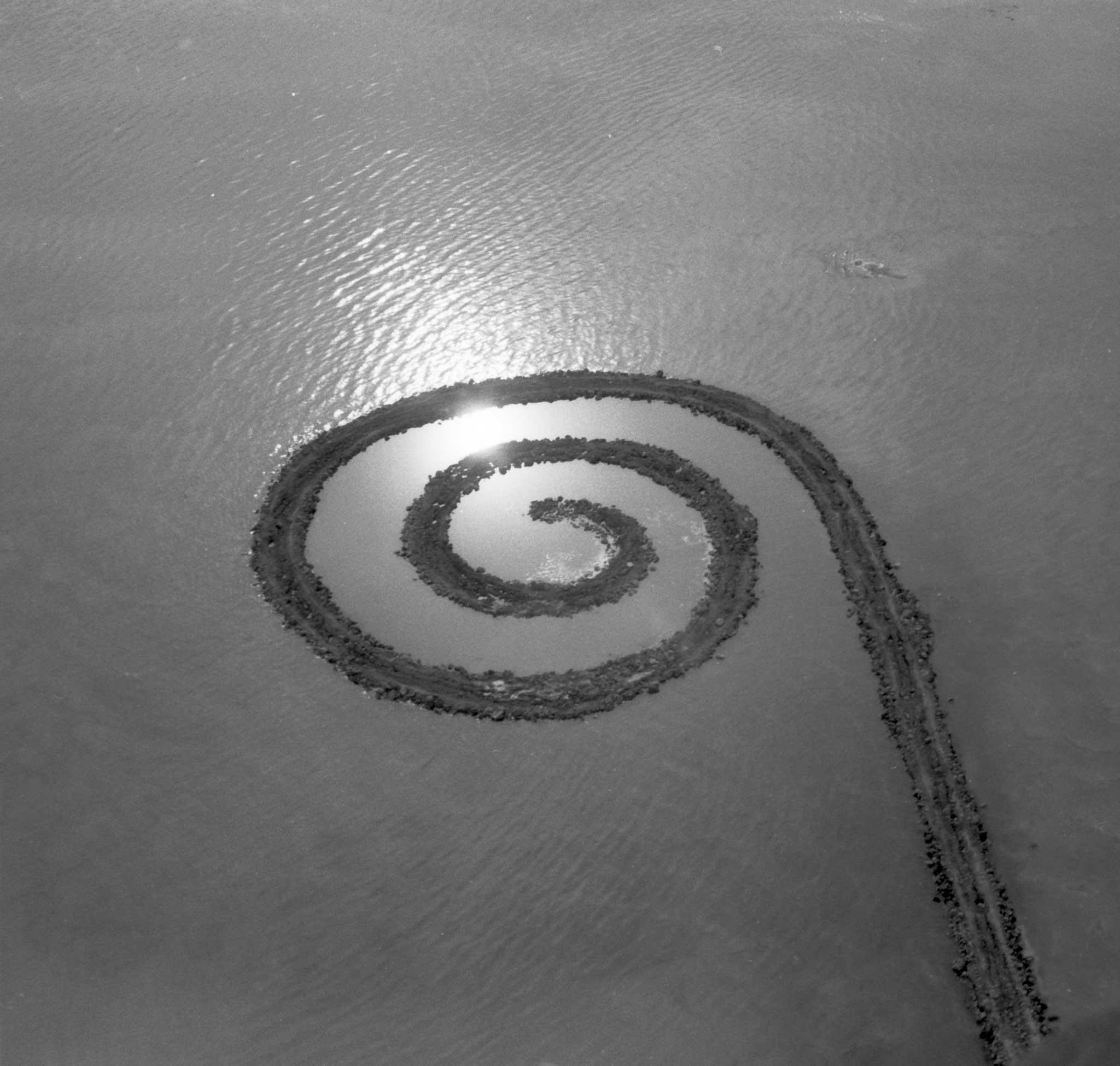 black and white, aerial image or an earthen jetty with a spiral termination extending into a body of water