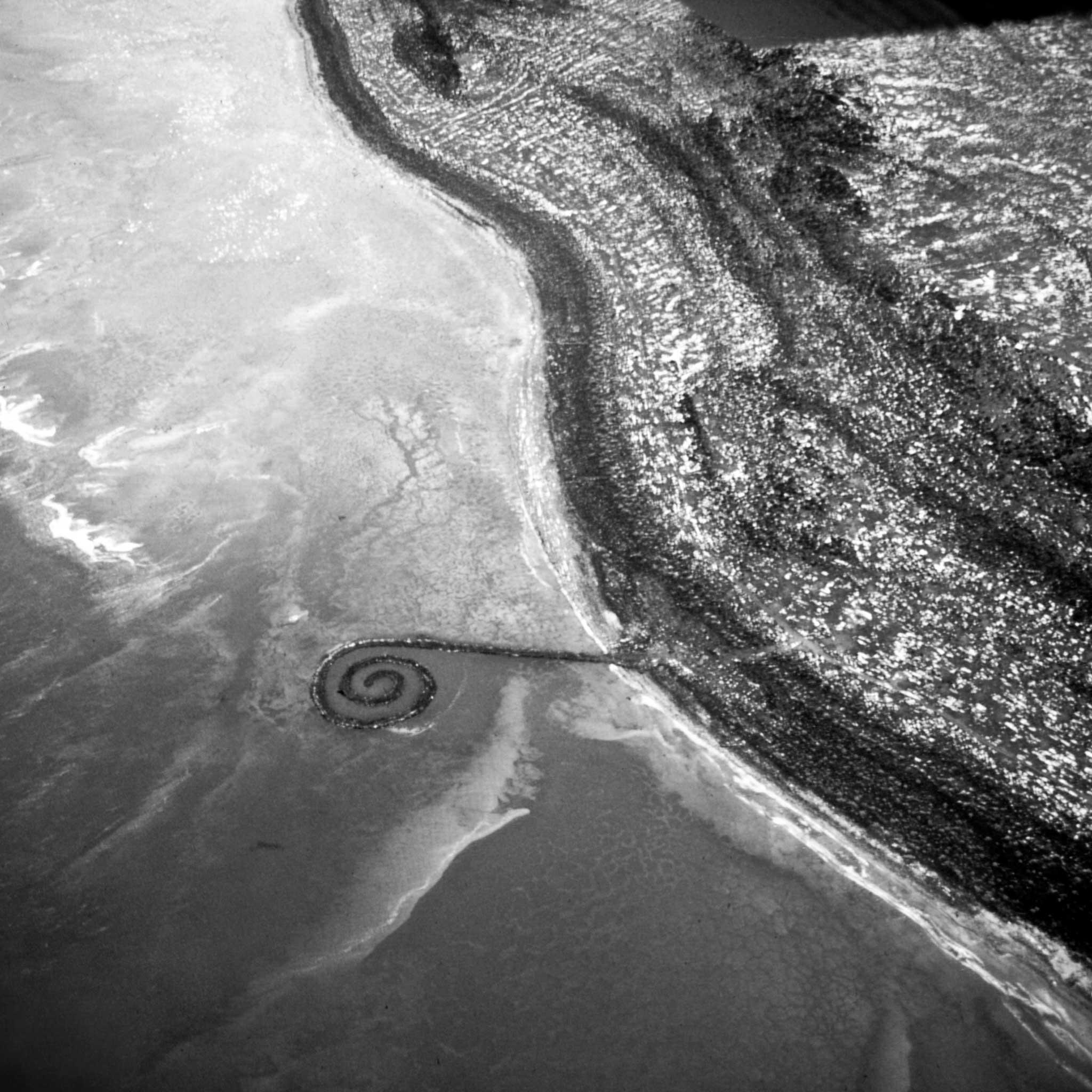 black and white, aerial image or an earthen jetty with a spiral termination extending out from the shore into a body of water