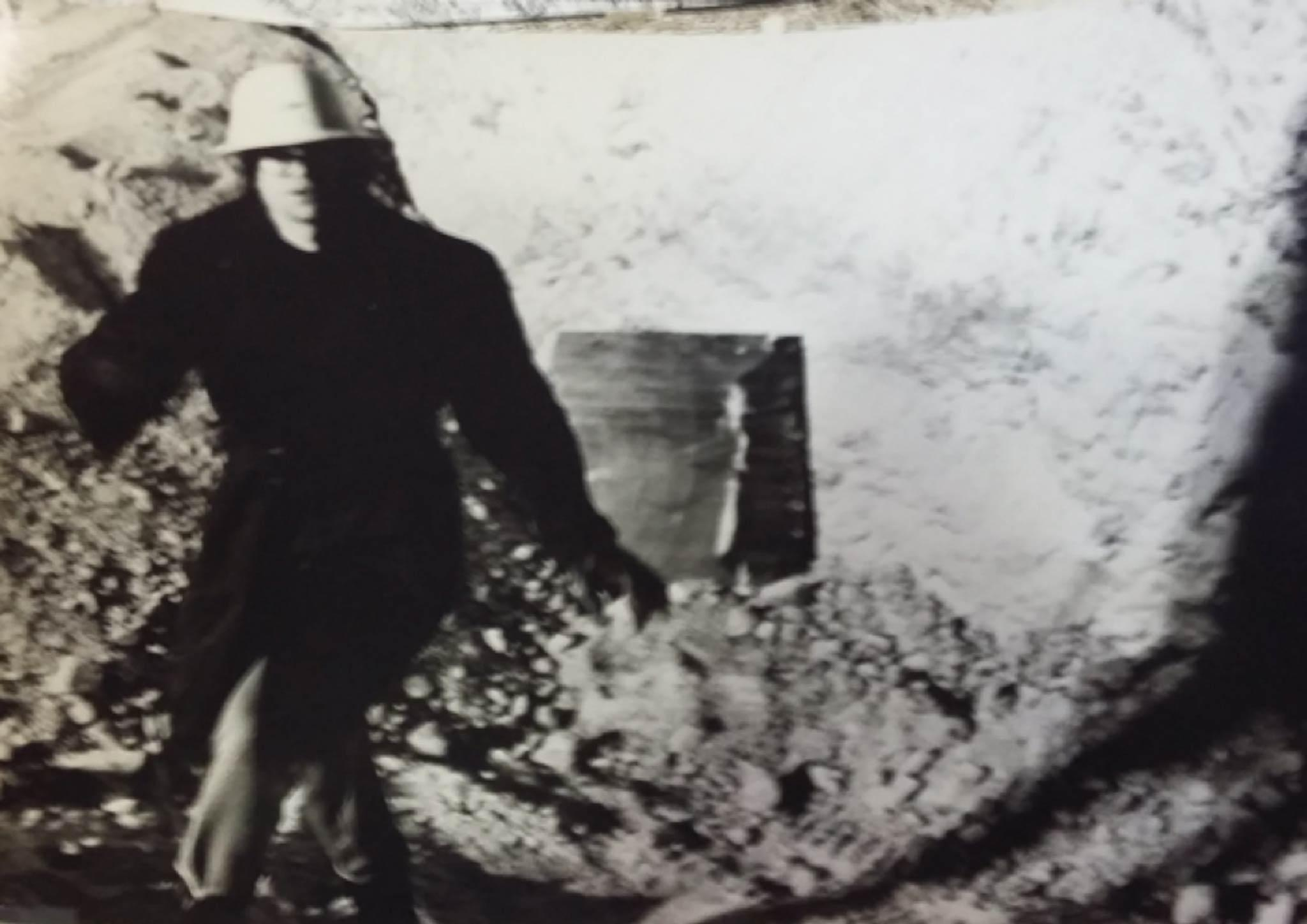 person wearing a large black coat and white hard hat looks at the camera with an obscure earthen background behind.