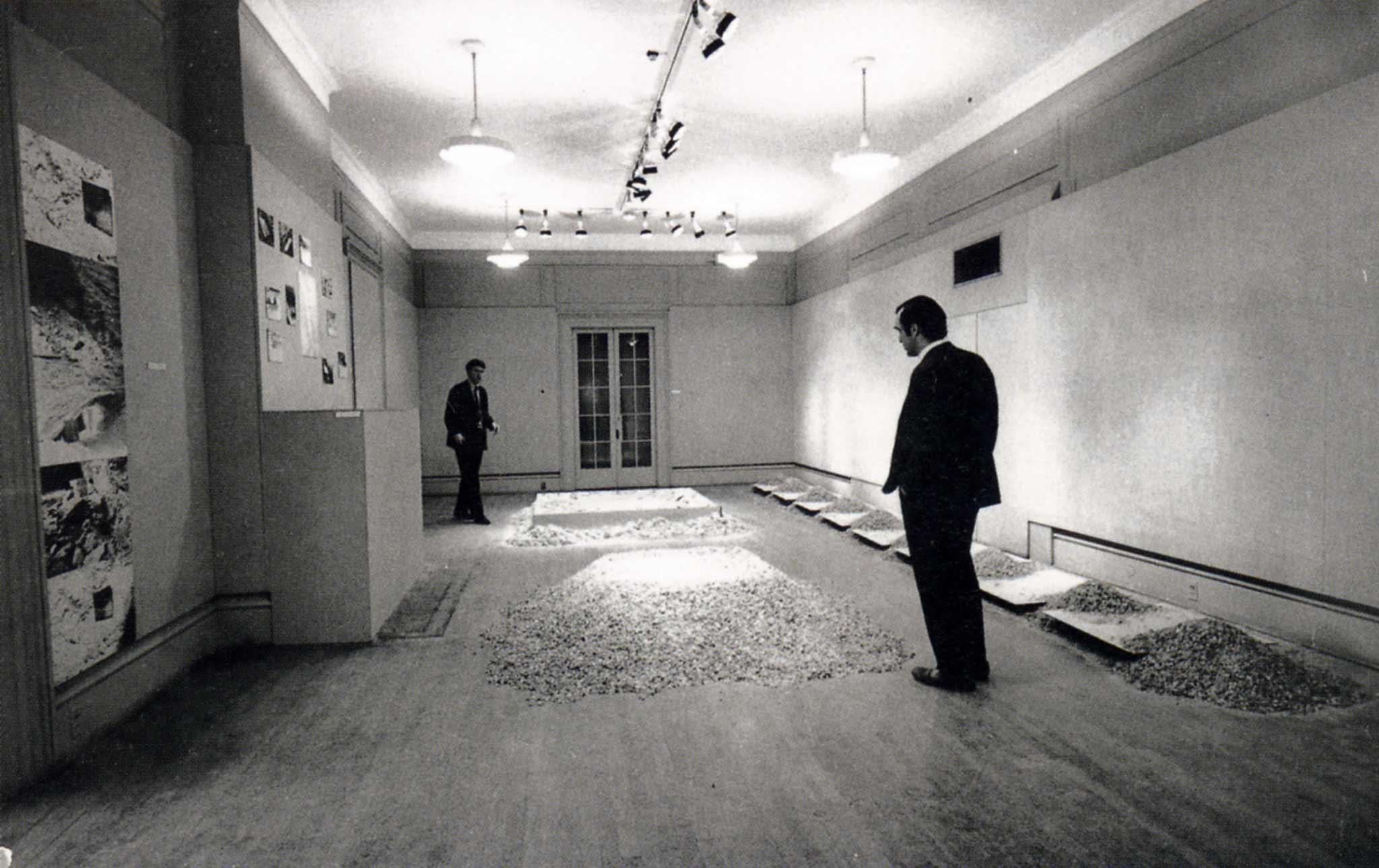 two figures in a room filled with sculptures made of salt and mirrors on the floor and photographs on the wall, black and white