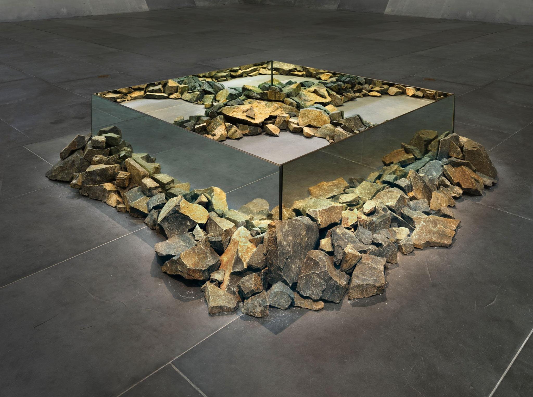 sculpture made using rocks and mirrors placed on the ground in a square shape