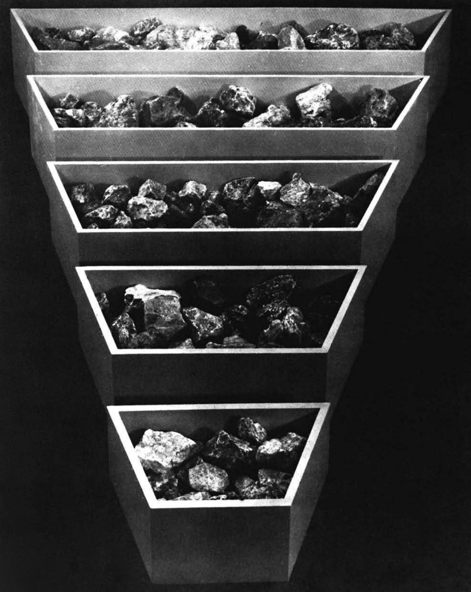 five polygon shaped bins arranged from largest at the top to smallest at the bottom filled with rocks