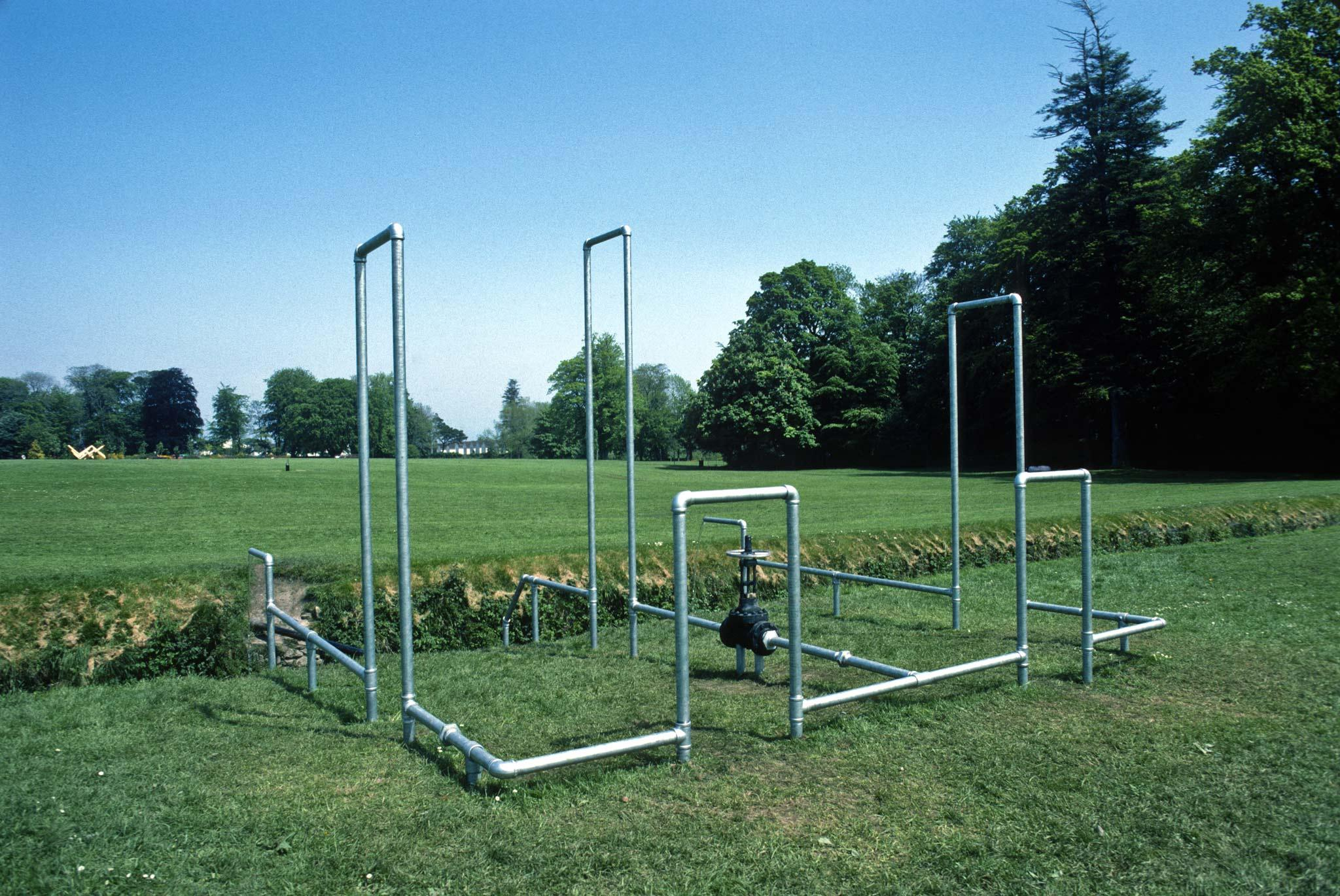 galvanzied pipes organized into rectilinear structures in a field outside a large home in Ireland