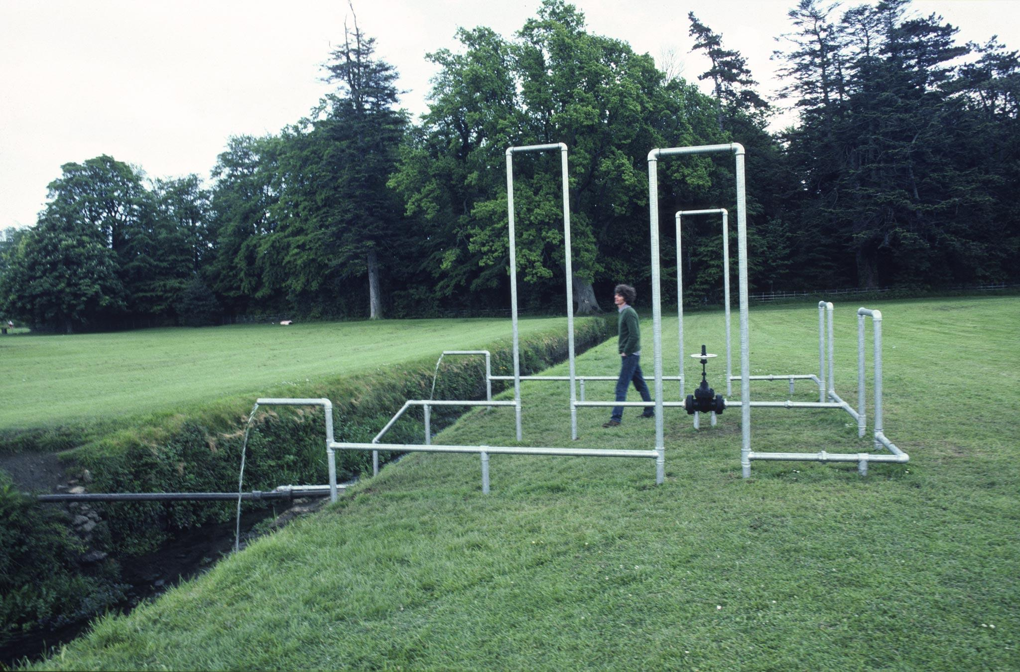 figure walking amongst galvanzied pipes organized into rectilinear structures in a field outside a large home in Ireland