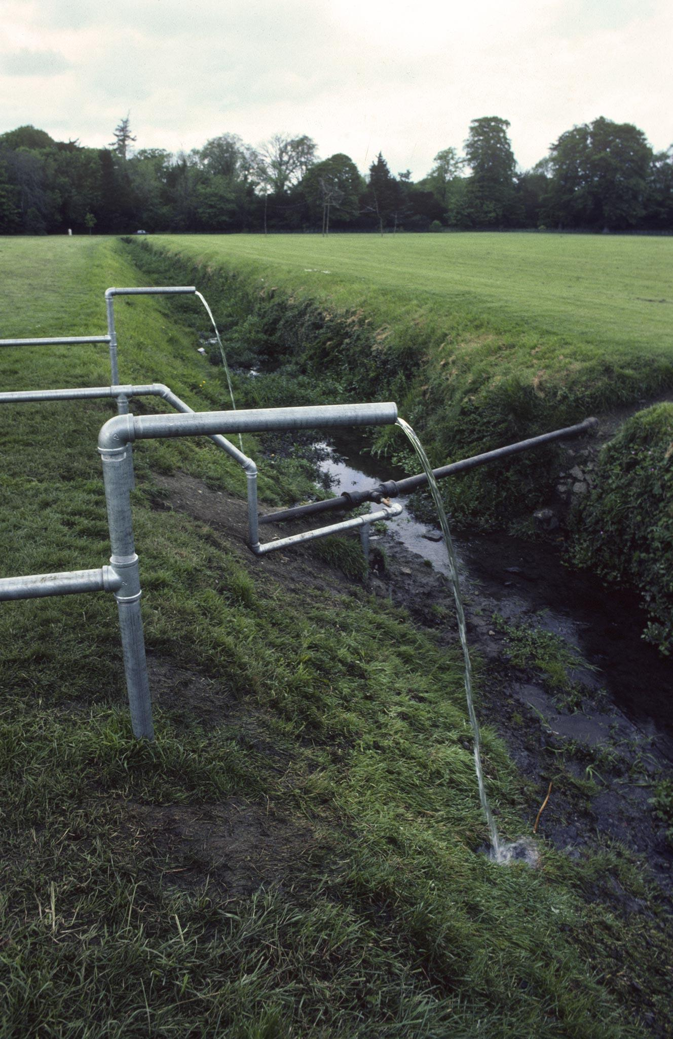 Water flowing from two galvanized pipes and dropping down into a muddy ditch