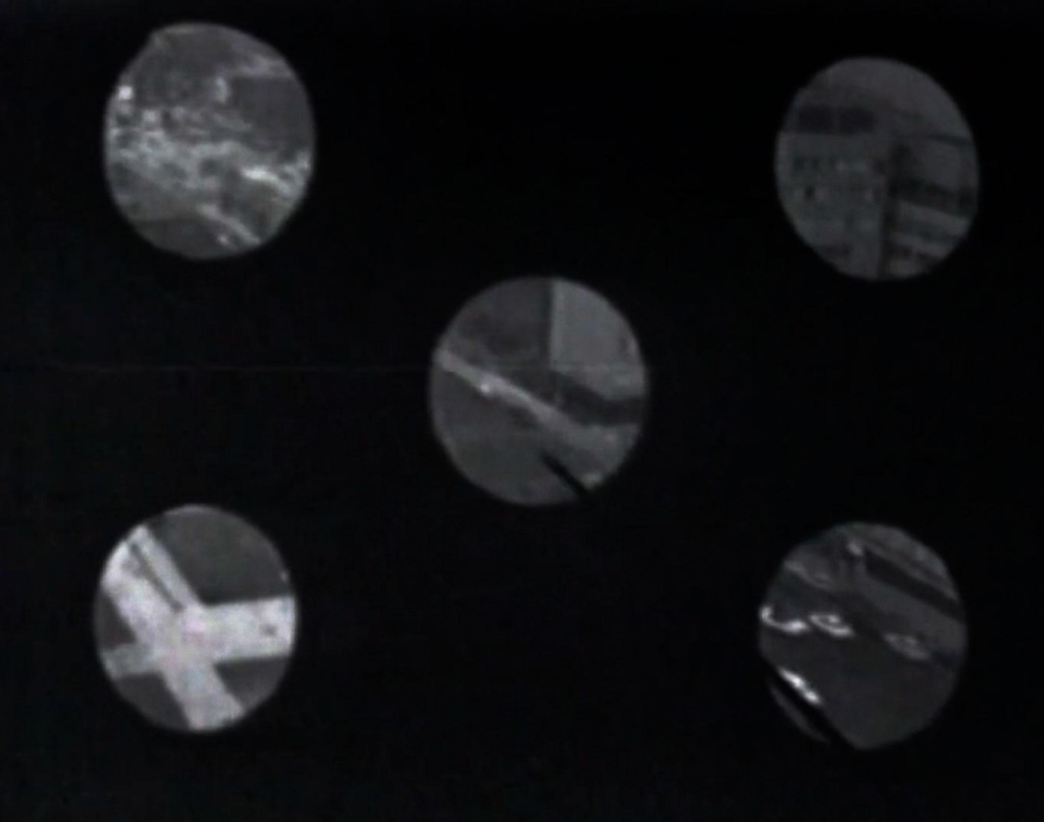 "five black and white circles arranged in an ""x"" formation on a black background that show details of an urban scene"