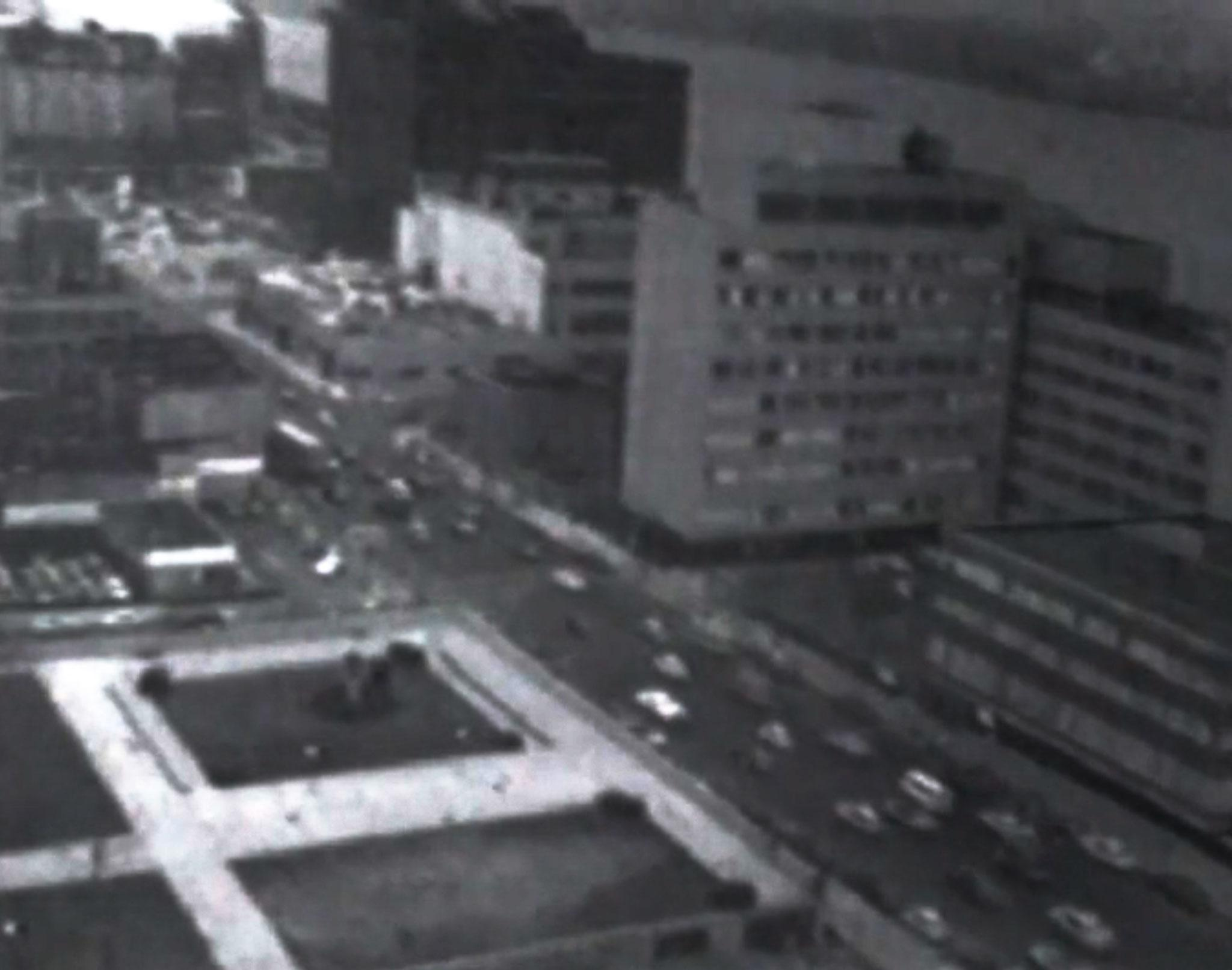 black and white urban scene from a high vista featuring buildings and a busy road
