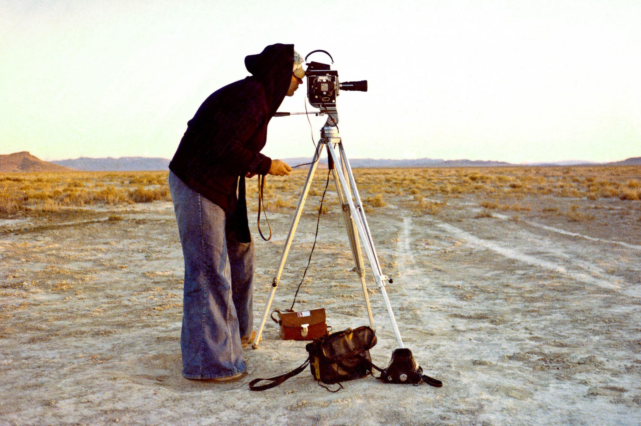side angle of a figure standing looking through a film camera on a tripod while out in the desert