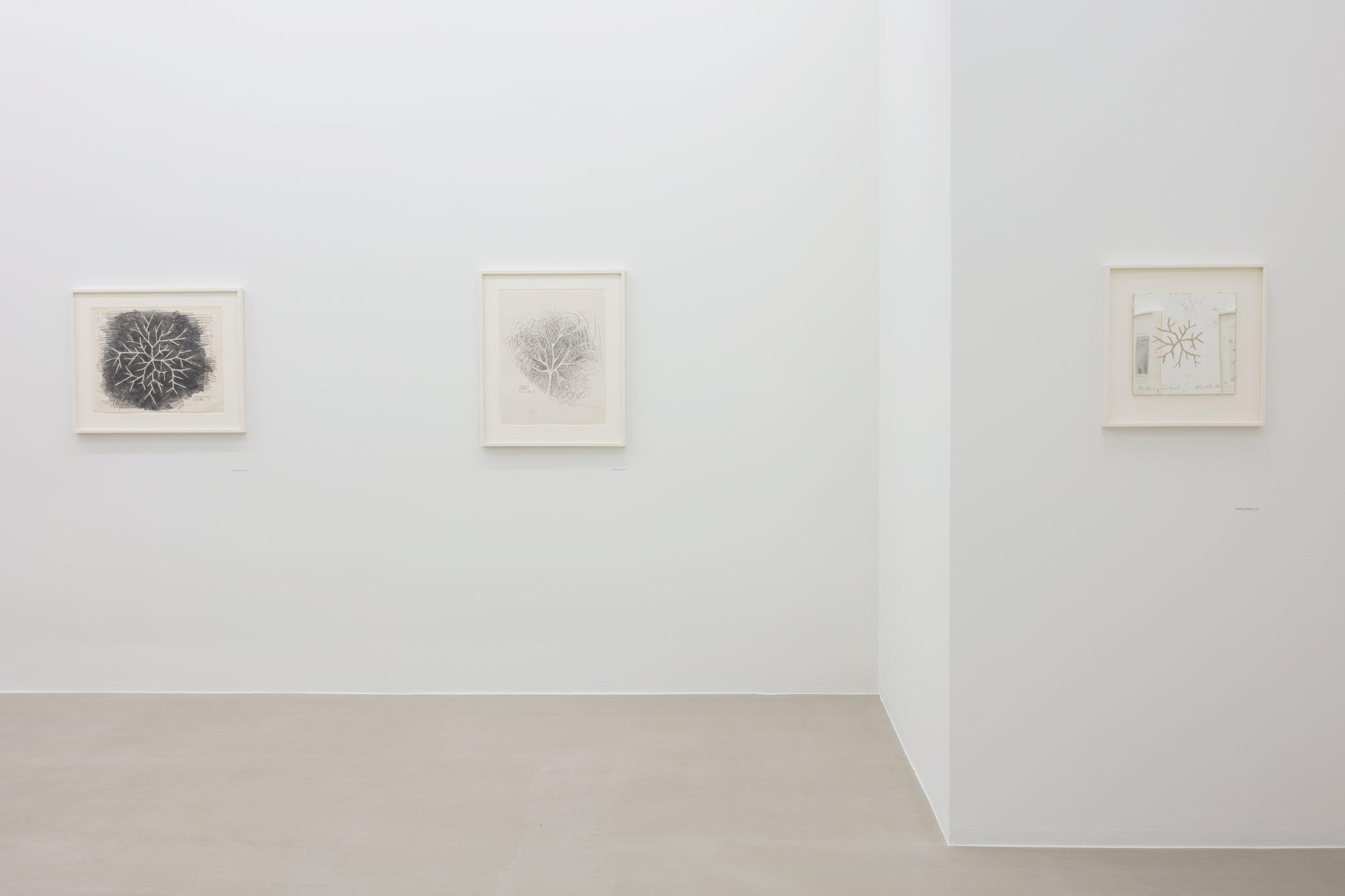 three black and white artworks hanging on the white walls of an art gallery