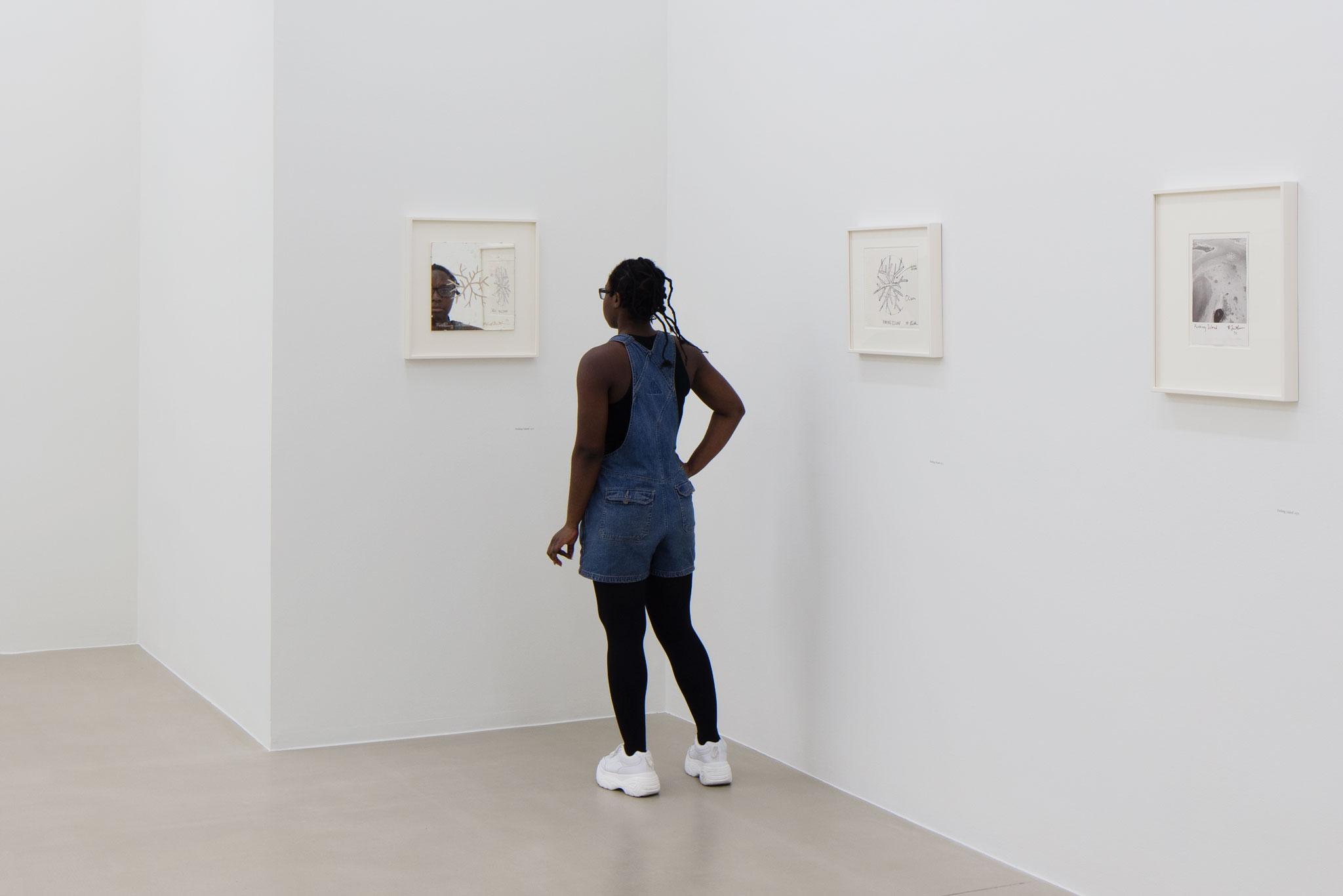 figure stands looking at small mirrored artwork on the white wall of an art gallery