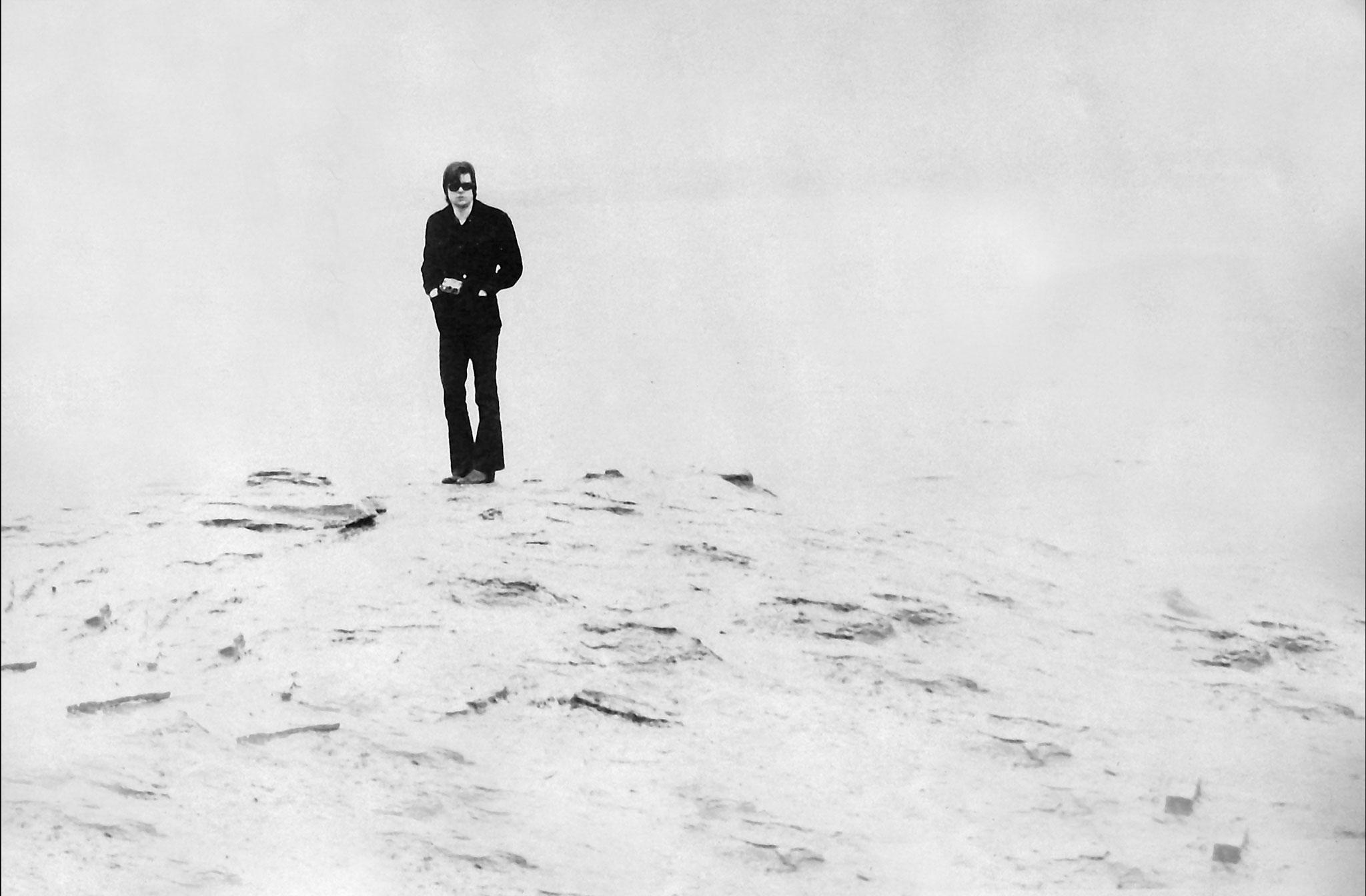 black and white: a figure wearing dark clothes stands on the edge of small outcrop of land with water behind.
