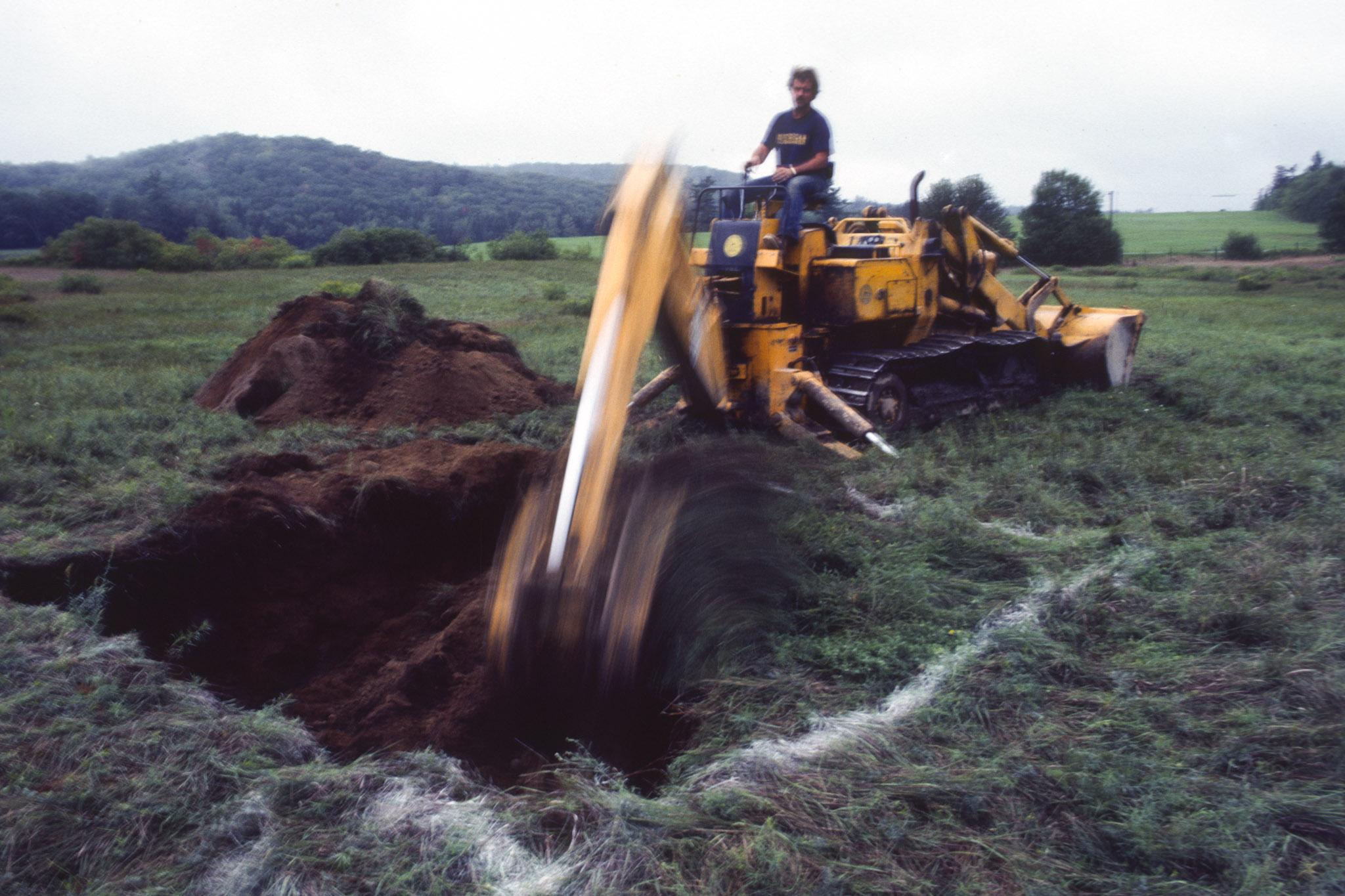 a large digging machine digs a square hole in a green grassy field