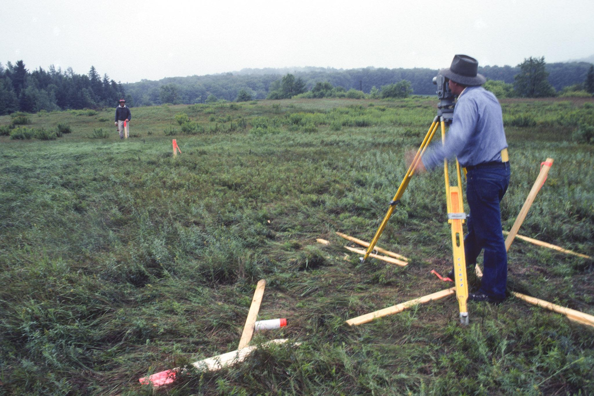 two figures stand far apart in a green field, looking through surveying equipment