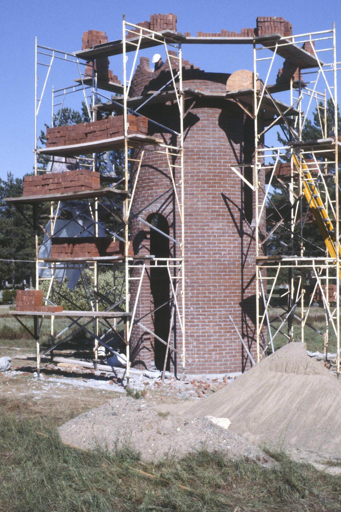 Construction showing scaffolding around a large circular tower made of brick