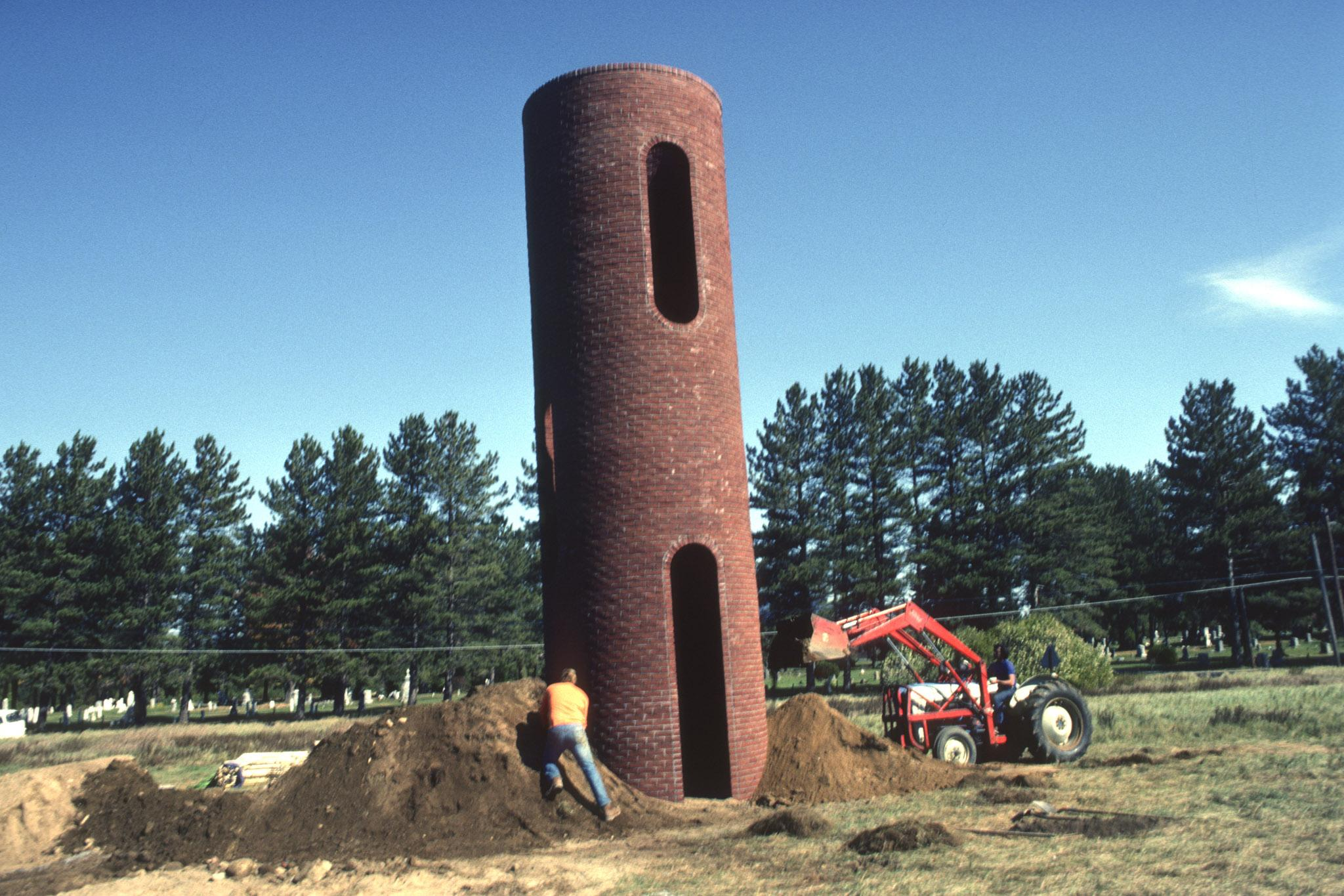 construction of a large cylindrical tower made using brick and two workers piling dirt around the base