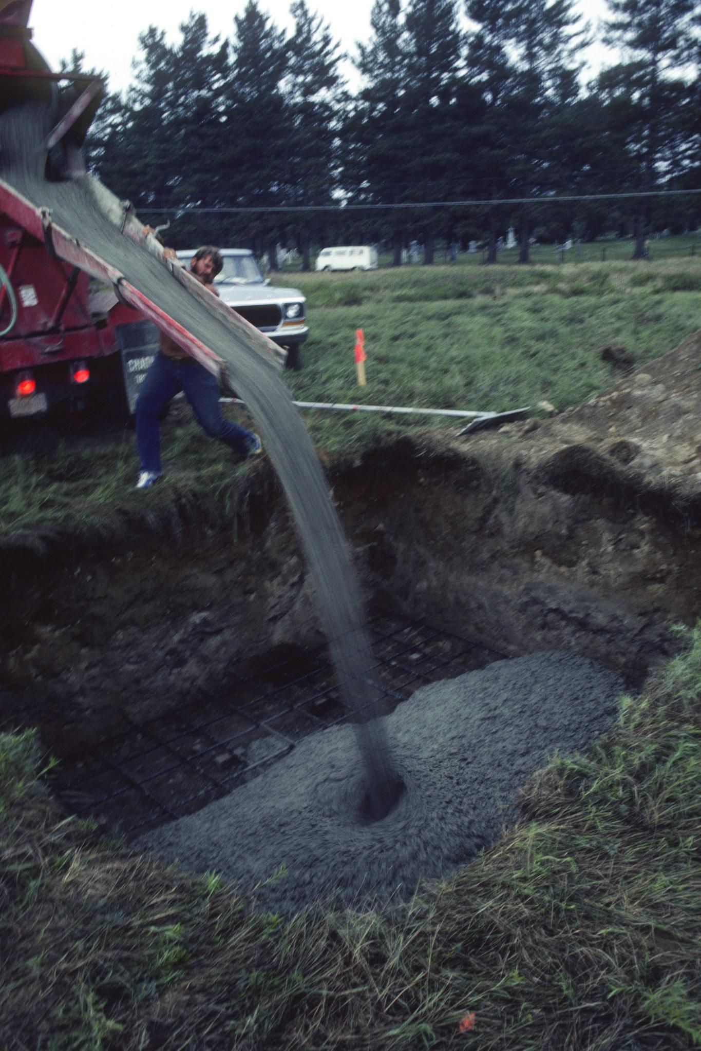 pouring concrete out of a chute into a square hole in a green grassy field