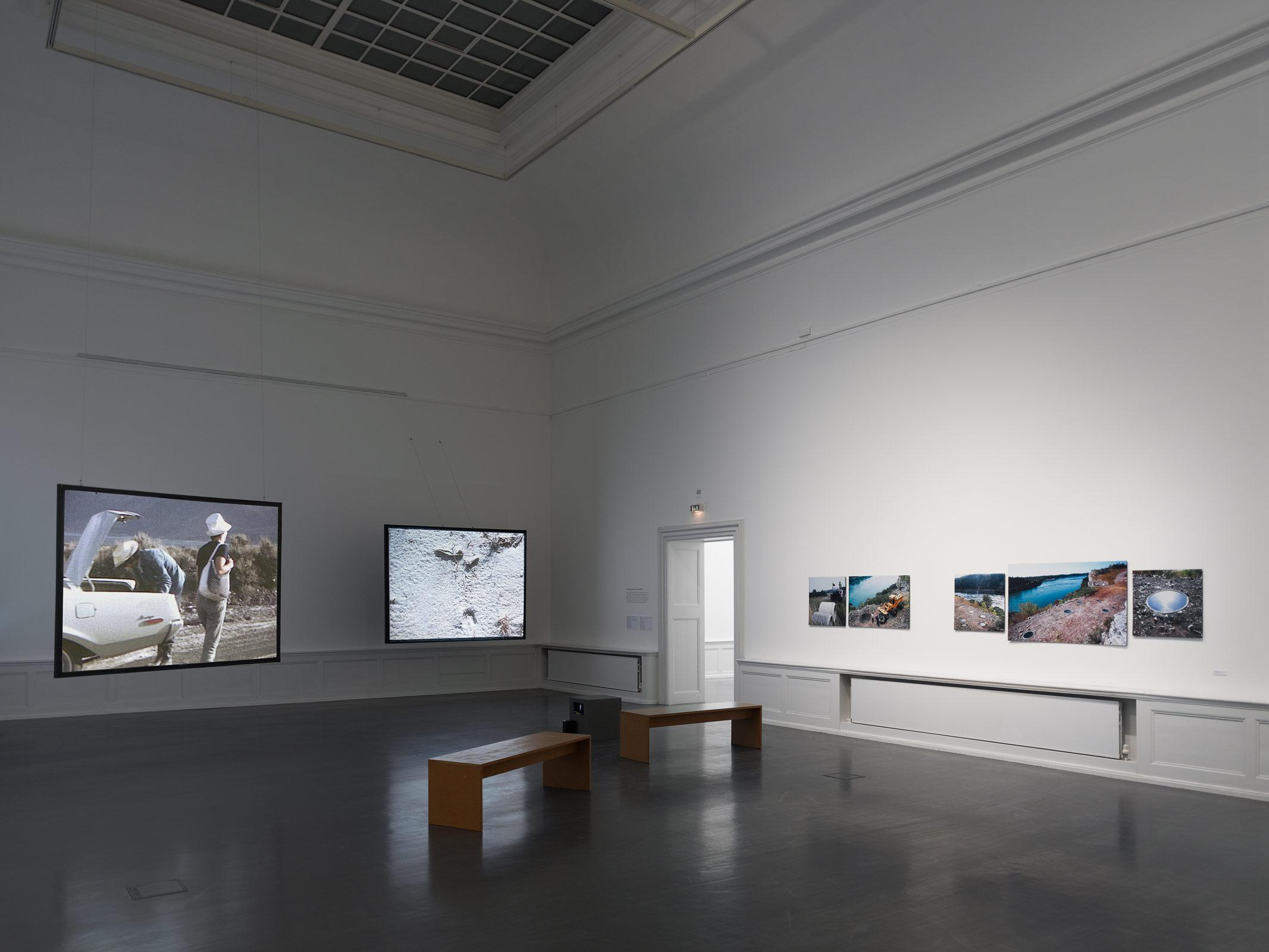 A large white walled room with benches and projected images on two hanging screens and images on the wall.
