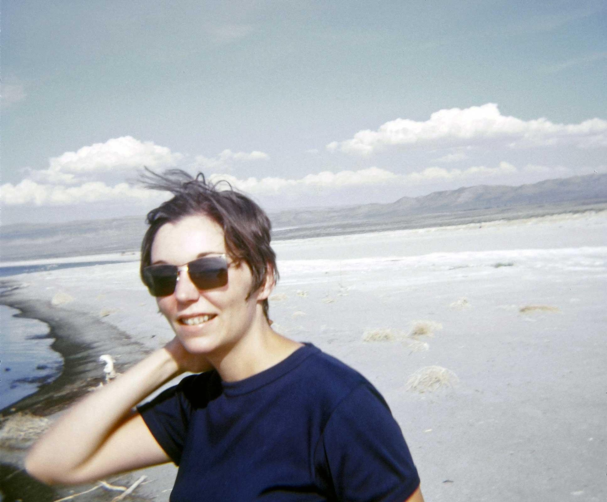 Nancy Holt standing by shore of lake with sunglasses on and short brown hair.