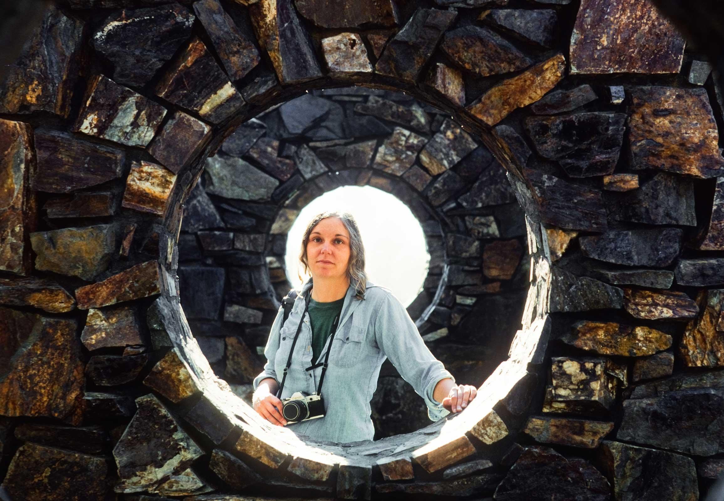 Nancy Holt standing in a circular hole at her work Stone Enclosure: Rock Rings