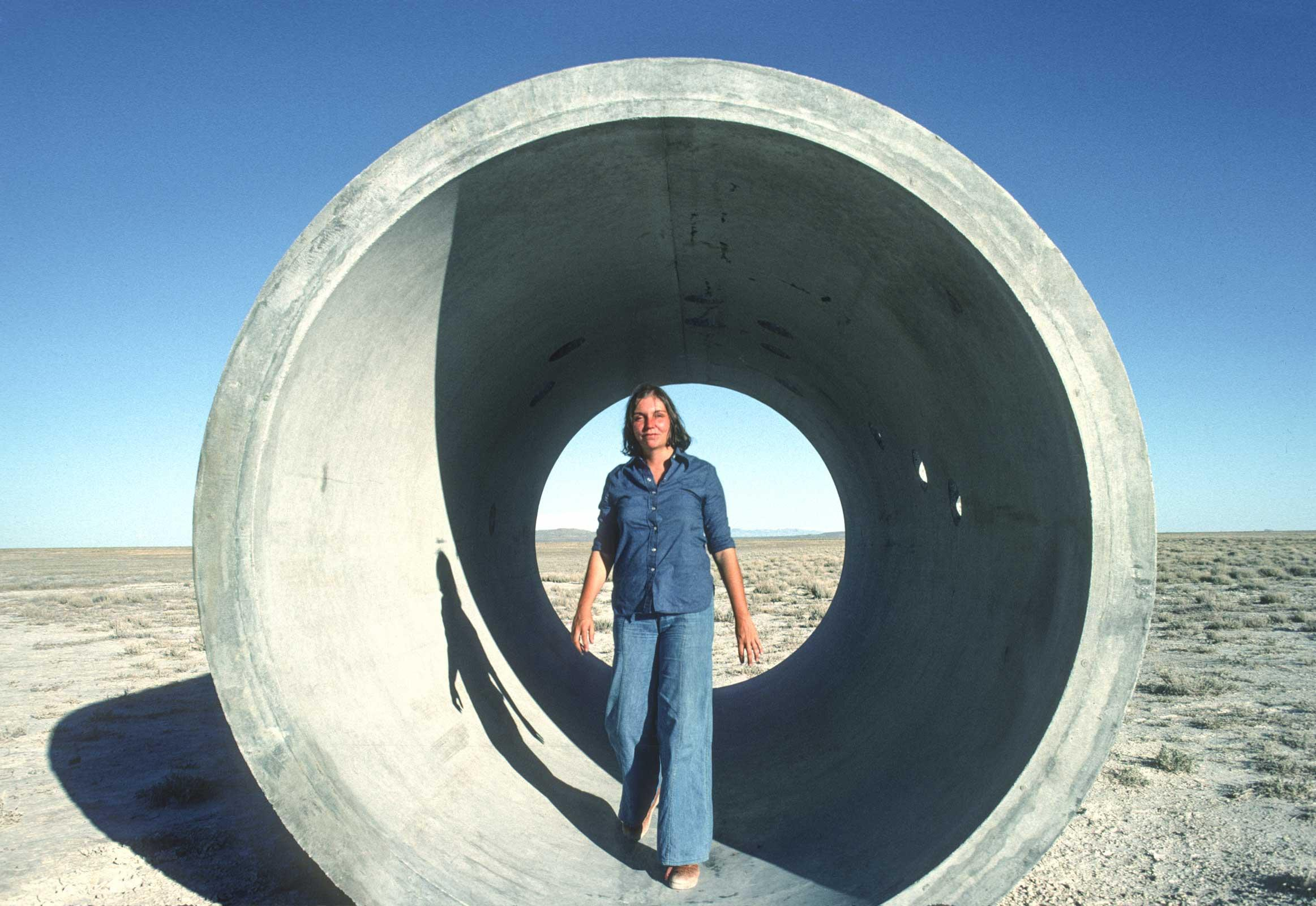 Nancy Holt standing inside one of the large tunnels that are part of Sun Tunnels.  Blue sky and sunny and Nancy is wearing a blue top and blue jeans.