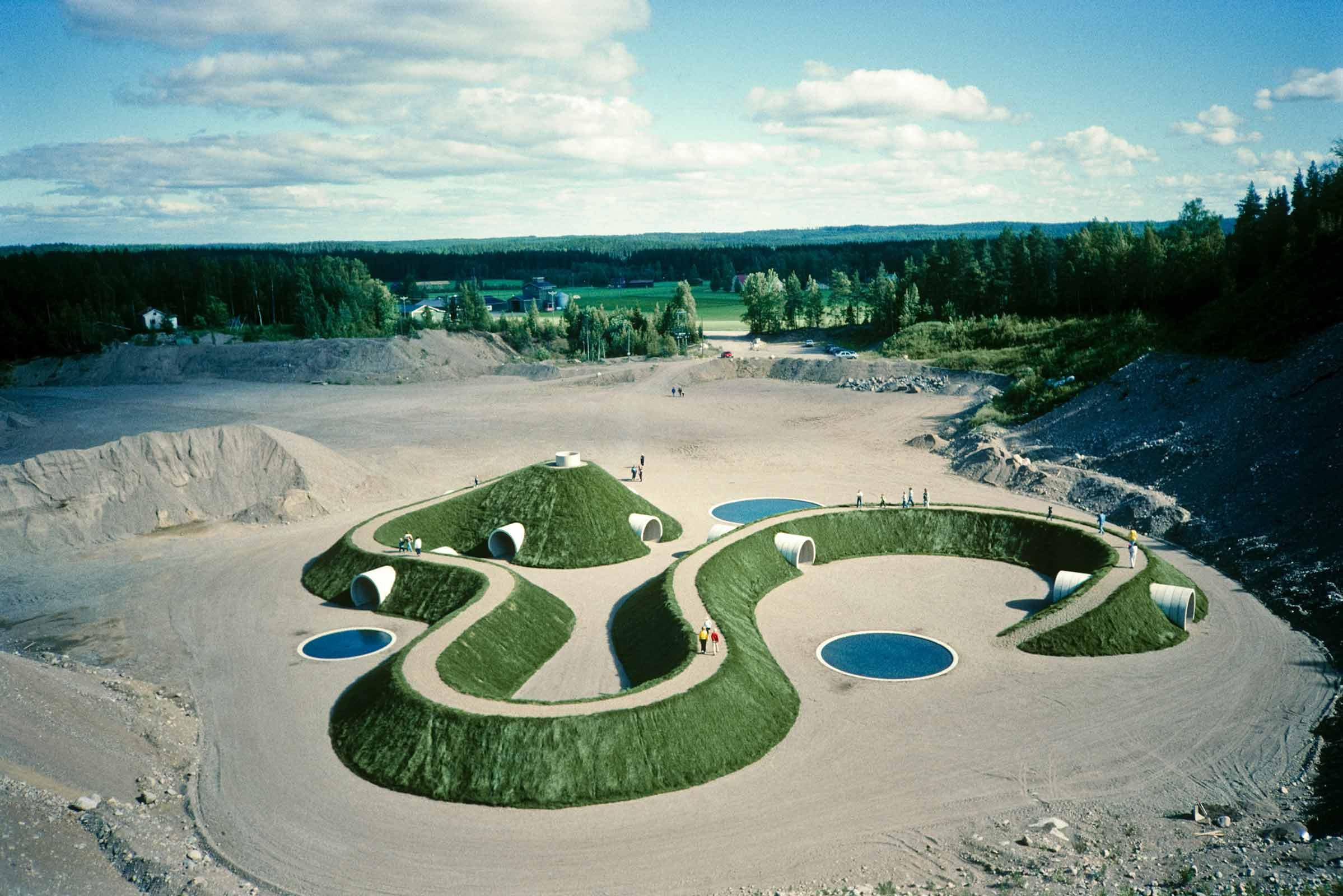 large earthwork sculpture made using earth, concrete, water, and grass with people moving around on top of it.