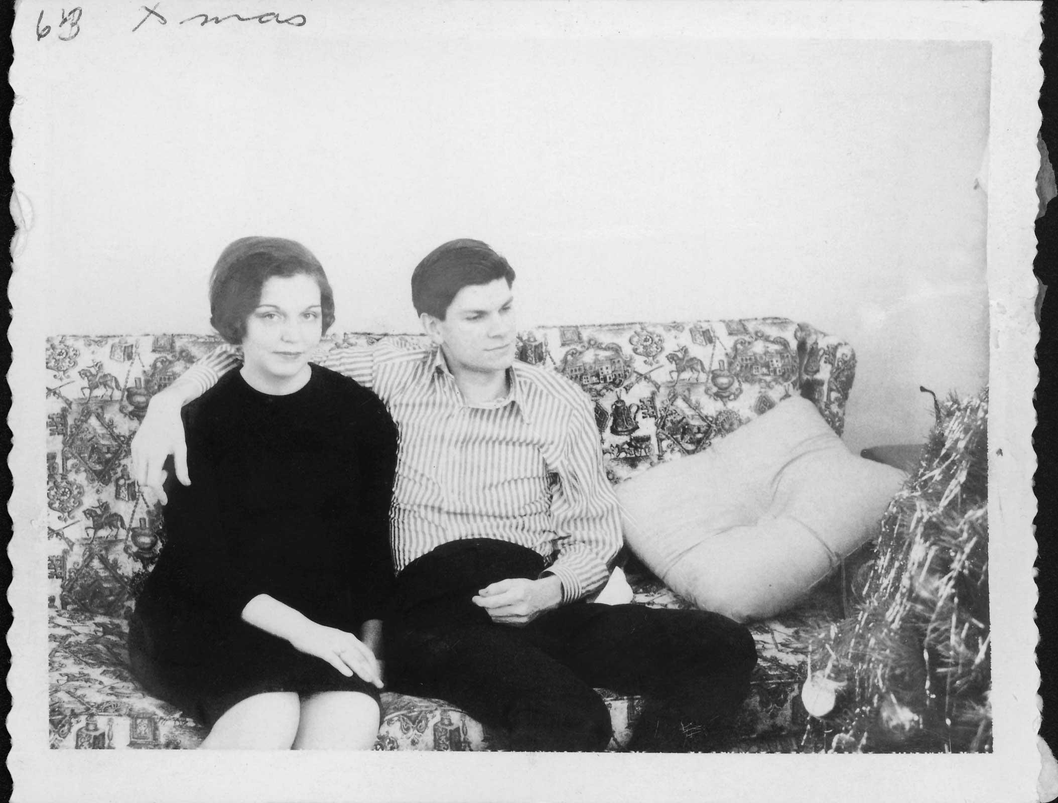 black and white photograph of a man and woman sitting on floral pattern sofa. Man has his arm around the woman and she is looking at the camera.