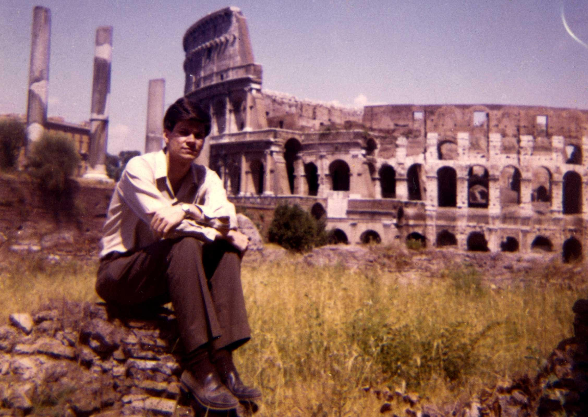 a young man seated on a rock with the Colosseum in Rome in the background